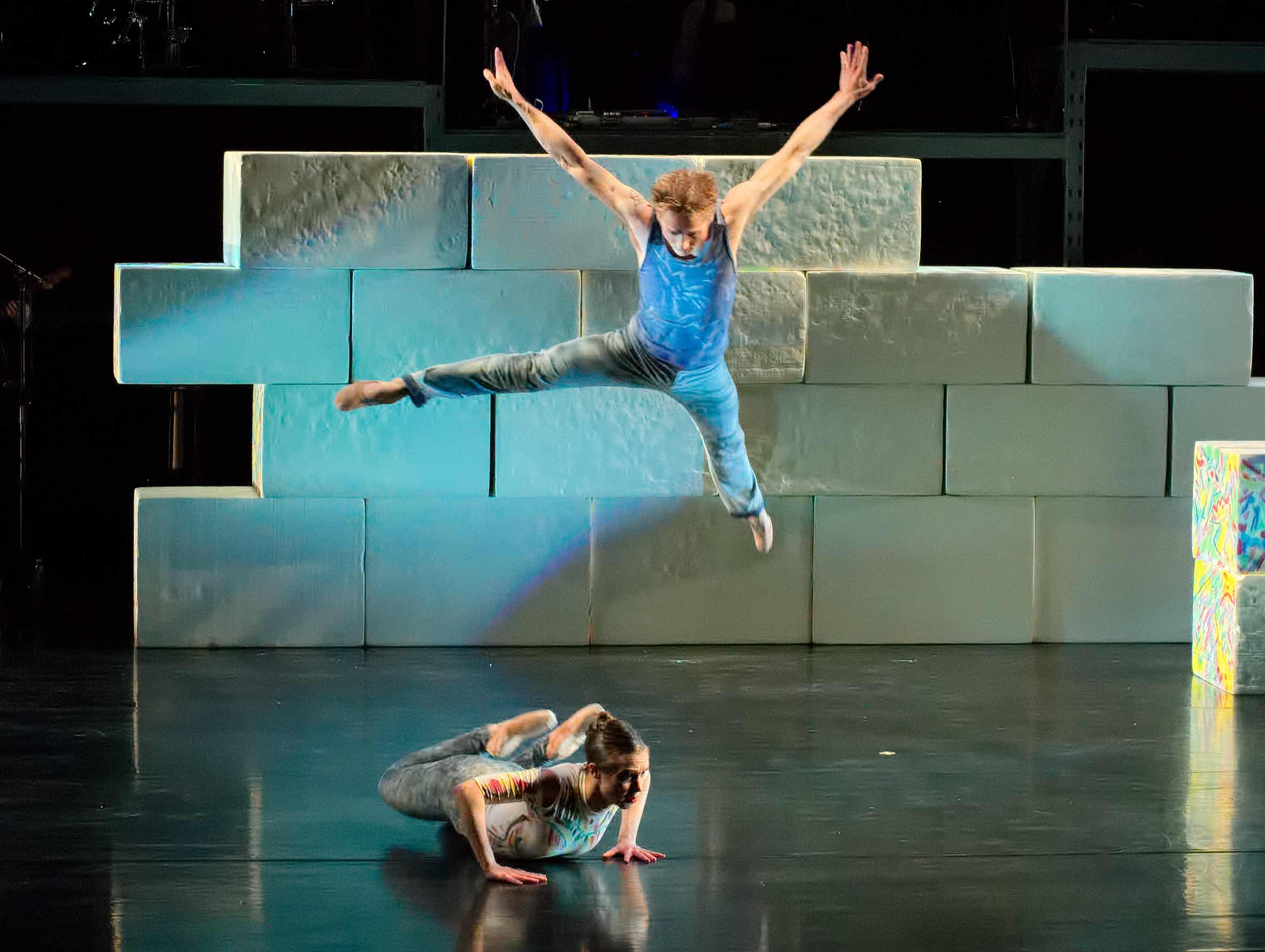 One dancer jumping over another in a scene from The Wall: A Rock Ballet