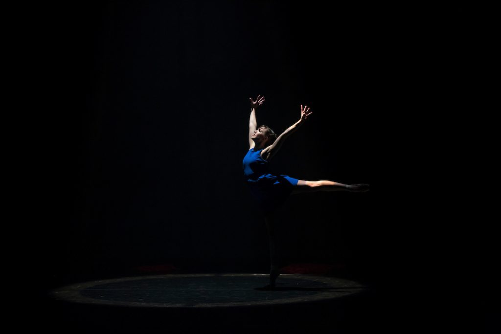 A single dancer illuminated from above from a performance of RED