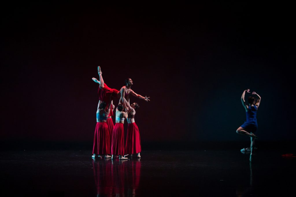 Dancers carrying another dancer during a performance of RED