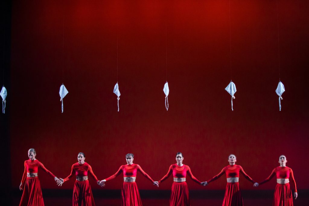 A line of dancers in red during a performance of RED